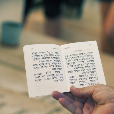 close up of person's hand holding open a booklet where the kaddish mourning prayer is shown in hebrew