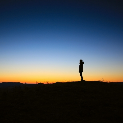 dark landscape with layers of blue sky transitioning to yellow orange with person standing in the distance in silhouette