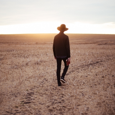 person in black jacket and pants with hat walking in dry wheat field with sun rising on horizon