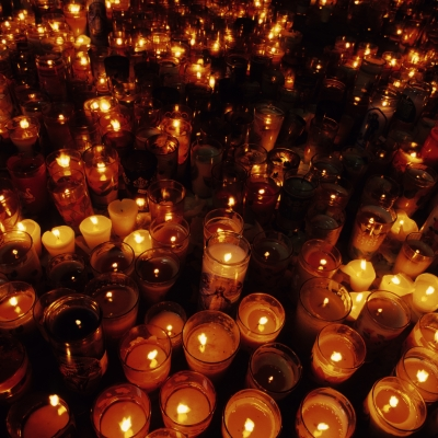 big group of lit candles in the dark