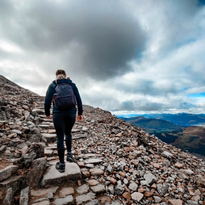 person shown hiking on rocky mountain from behind wearing backpack with clouds and mountains in the distance