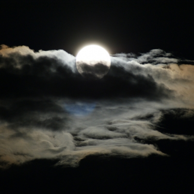 moon peeking out behind gray clouds