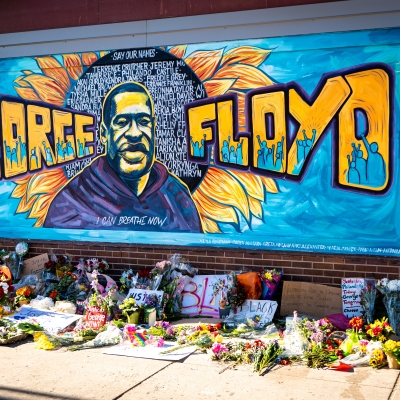 A George Floyd memorial that is painted in blue, yellow, and black on a wall
