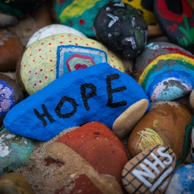"""many painted rocks are laying on top of one another. In the middle is a bright blue rock with """"HOPE"""" written in black letters"""