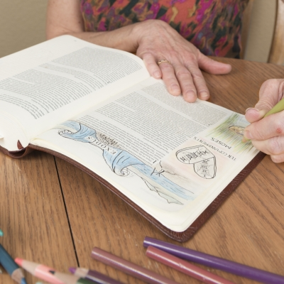 woman with wrinkled hands writing in journal