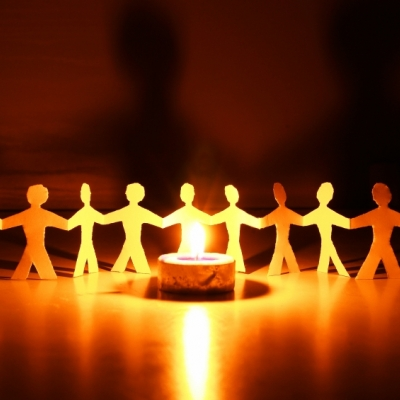 cut out of group of people holding hands next to a tea light candle