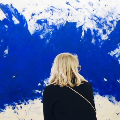 large white canvas with huge blue abstract splatter paint with woman standing in front shown from the back with medium length light blonde hair in black shirt looking off to the right