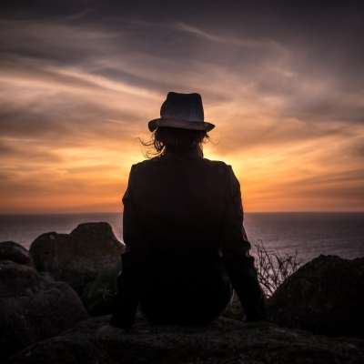 person shown from behind sitting among large rocks looking at ocean sunset