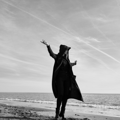 black and white photo of white blonde woman in oversized black coat with hood on, standing at the ocean shore, hands open to the sky, looking like she might be dancing or moving freely