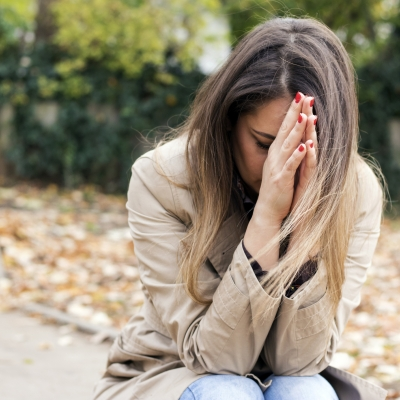A person with fair skin and dirty blonde long hair is crouched on the ground with their hands in a praying position in front of their face. Their head is bent down towards the ground. They are wearing a tan overcoat and there is a tan leather bag off to the side in the bottom right corner of the photo. They are outside and there are fallen leaves scattered over the ground in the background.