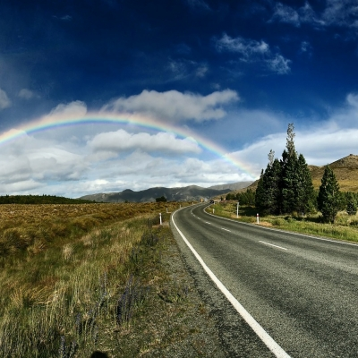 open road leading to rainbow and sky with clouds