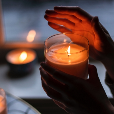 hands holding candle in glass glowing
