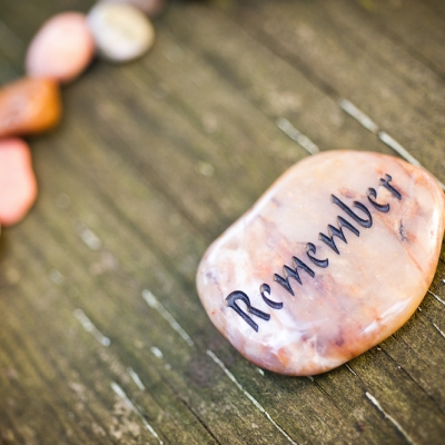 coral colored stone with the word remember on it