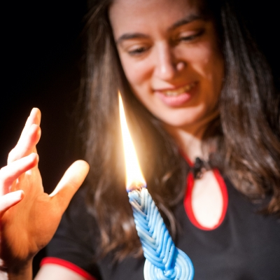 woman holding lit havdalah candle with hand feeling its warm nearby