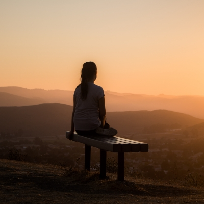 woman shown from behind sitting on bench on hill or mountain looking at sunset