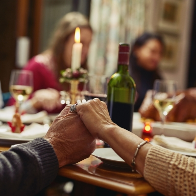 A shabbat dinner table with three guests is blurry in the background. In focus are the arms of two people holding hands. Shabbat candles are lit and we see a wine bottle as well.