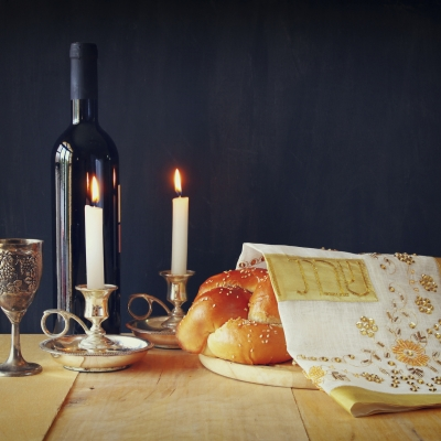 a kiddush cup, bottle of wine, lit shabbos candles and a covered challah with a white challah cover with gold embroidery