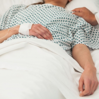 person lying on hospital bed with caregiver by their side