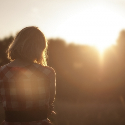 woman shown from behind looking at sunset and trees