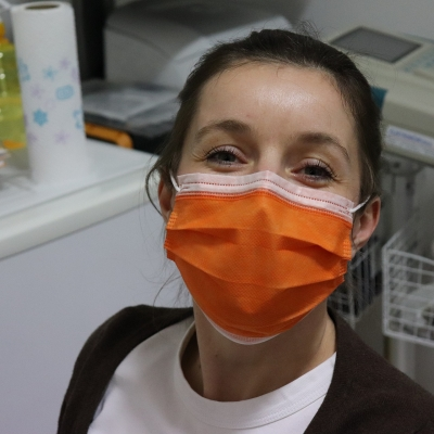 woman in hospital setting wearing orange surgical mask and smiling