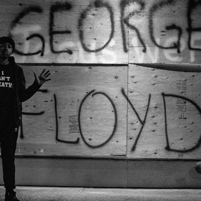 """a Black boy stands in front of plywood painted with George Floyd's name. He is dressed in all black, is hands are up and his hoodie says """"I CAN'T BREATHE"""""""