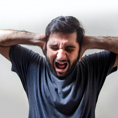 a person with short, dark hair and a trimmed beard and mustache is shouting with their eyes clenched shut and their hands pressed against their ears. They are wearing a navy blue t-shirt and standing in front of a white background