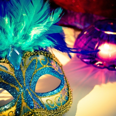 turquoise and gold venetian mask next to tea light in purple glass