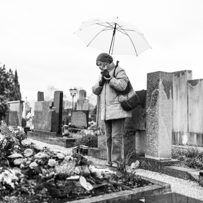black and white photo of older woman standing by a gravesite holding umbrella