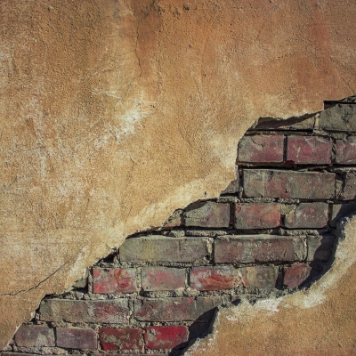 wall with crack showing brick behind it