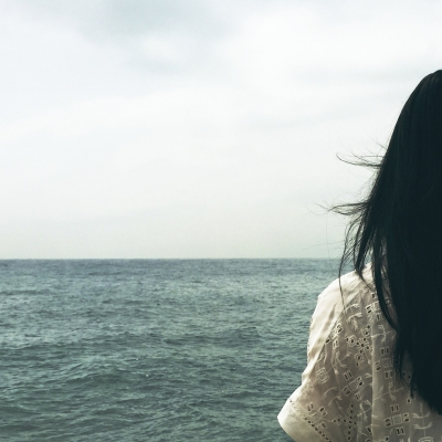 woman shown from the back with long black hair facing the ocean