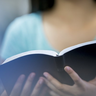 woman holds open book