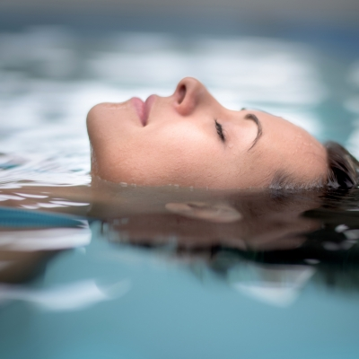 close up of woman's face, eyes closed, as she floats peacefully in water
