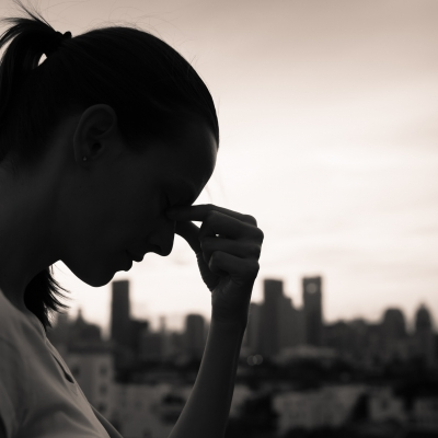woman in silouette with head down, fingers on forehead