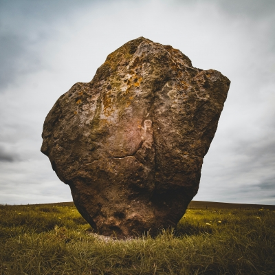 a tall brown rock sits in a field against a cloudy sky
