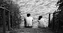 man and woman sitting by a lake; black and white photo; distance between the people