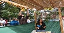 people decorating sukkah with decorations