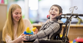 smiling woman playing with young boy smiling in a wheelchair