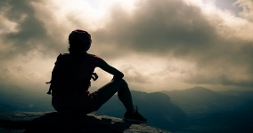 silhouette of person sitting and looking at clouds after hiking up a mountain