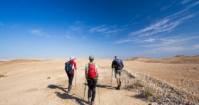 three people hiking in the desert