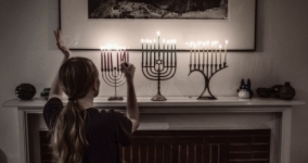 girl lighting hanukkah candles on mantel
