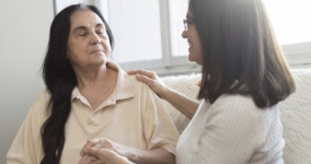 caregiver with hand on woman's shoulder offering support