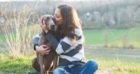 woman kissing her dog sitting in a field