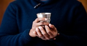 hands holding a silver kiddush cup