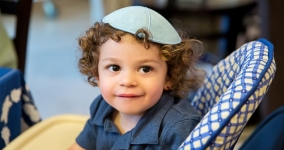 little boy with long curly hair wearing kippah