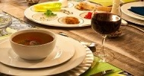 passover table with matzoh ball soup, a glass of wine and the seder plate