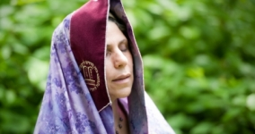 woman praying outside draped in purple tallit eyes closed