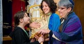 three generations of women holding the torah