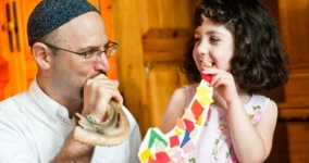 father wearing kippah blowing shofar while smiling at young daughter also blowing toy shofar