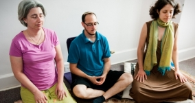 three people meditating with crossed legs and eyes closed, sitting on pillows
