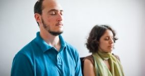 two people meditating with eyes closed